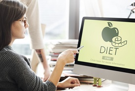 Image of employee looking at diet on computer screen indicating employer wellness programs