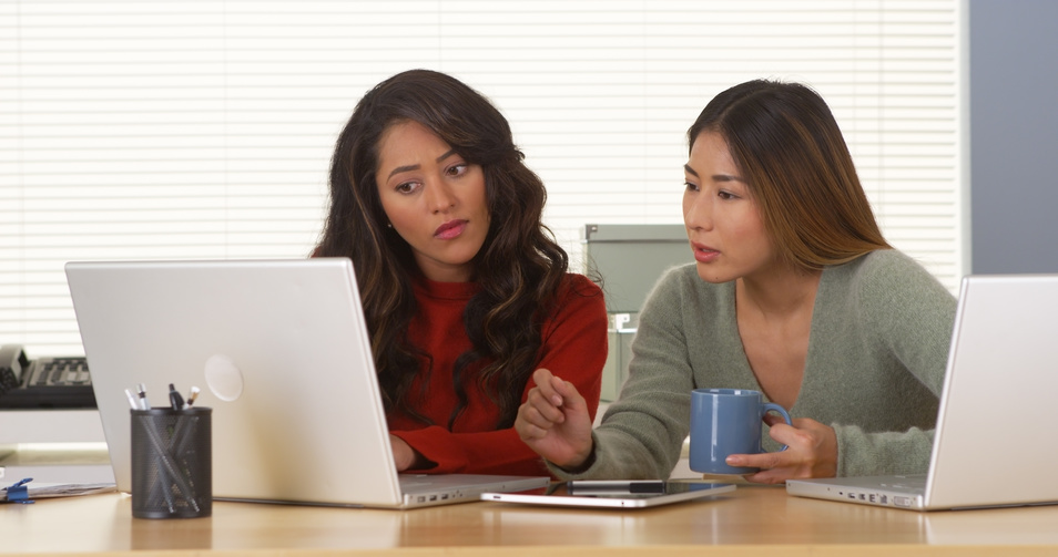 Mexican  and Japanese women working on laptop
